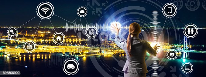 istock smart city panorama and business person controlling futuristic GUI, abstract image visual 696806900