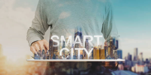 Smart city technology, a man using digital tablet, and modern buildings hologram stock photo