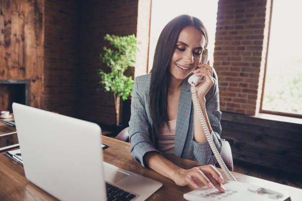 Elegante, inteligente y señora agente inteligente en gris blazer a cuadros marca un número de teléfono para contactar con el Departamento de entrega y enviar el pedido al cliente - foto de stock