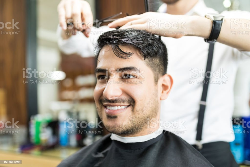 Smart Client Smiling While Stylist Cutting His Hair In Salon