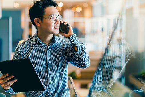 smart confidence asian startup entrepreneur business owner businessman smile hand use smartphone woking in office background