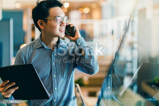 smart confidence asian startup entrepreneur business owner businessman smile hand use smartphone woking in office background