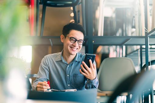スマホを見て微笑む男性の写真|KEN'S BUSINESS|ケンズビジネス|職場問題の解決サイト