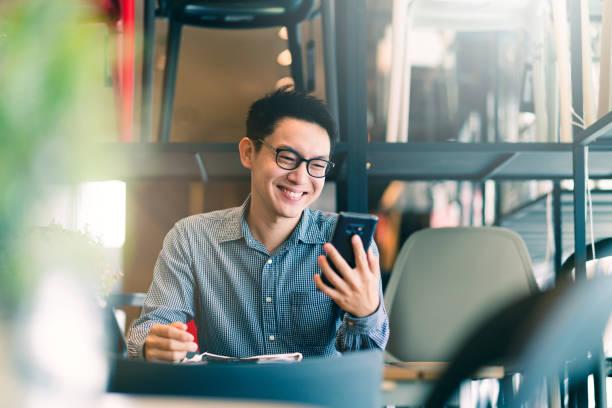 聰明自信 亞洲 創業企業家 企業主 商人 微笑 手 使用 智慧手機 在 辦公背景 - 亞洲 個照片及圖片檔