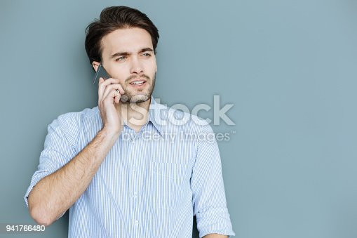 Phone communication. Smart nice confident man standing and putting a phone to his ear while making a call