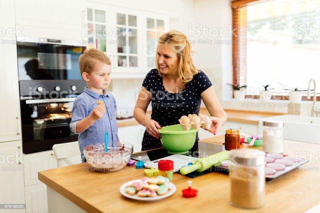Intelligent joli enfant aidant la mère dans la cuisine - Photo