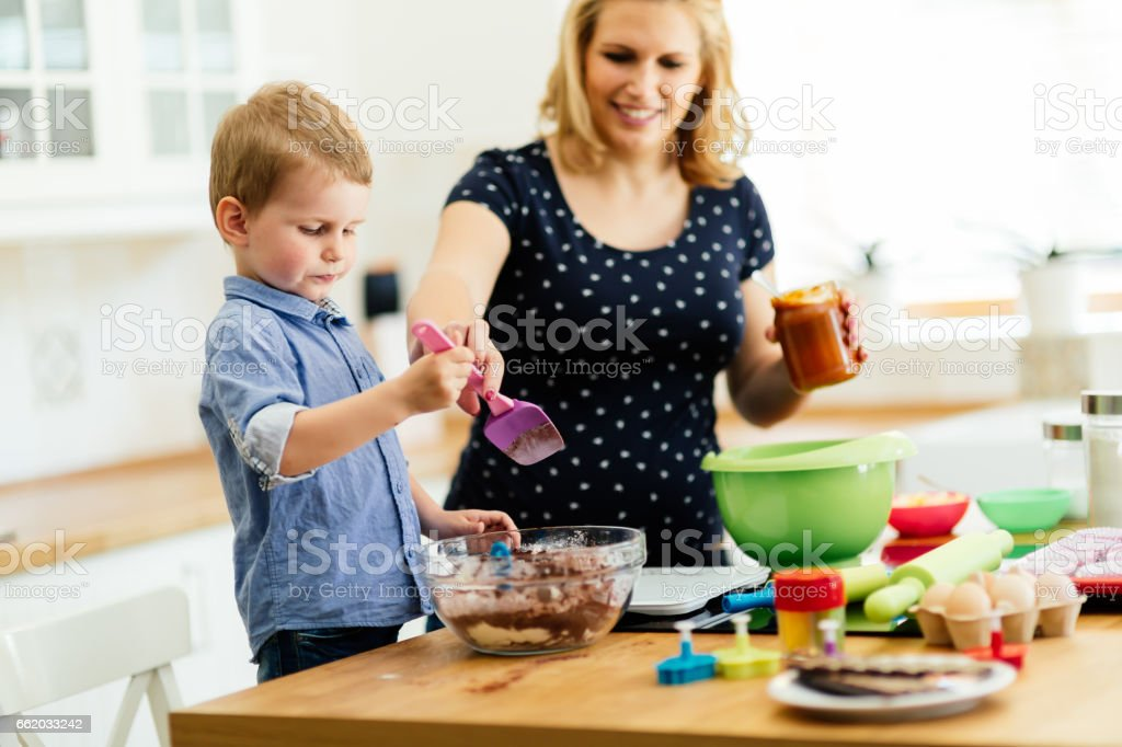 Smart cute child helping mother in kitchen preparing cookies royalty-free stock photo