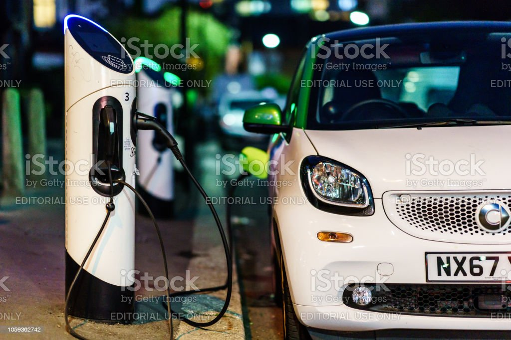Smart electric car charging in the London Street st night. London, UK - October 20th, 2018: Smart electric car charging in the London Street st night. Alternative Fuel Vehicle Stock Photo
