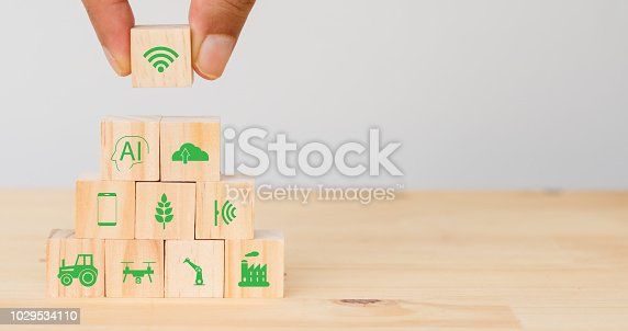 1127437312istockphoto smart farm or agriculture futuristic technology concept, Hand man put the icon connect, icon including wireless wifi, ai or artificial intelligence, cloud, phone, sensor, truck, robot, drone, factory 1029534110