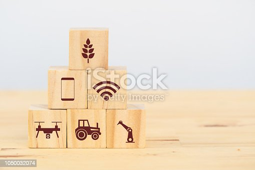1127437312istockphoto smart farm or agriculture futuristic technology concept, wooden cube icon connect, icon including wireless wifi, ai or artificial intelligence, cloud, phone, sensor, truck, robot, drone, factory 1050032074