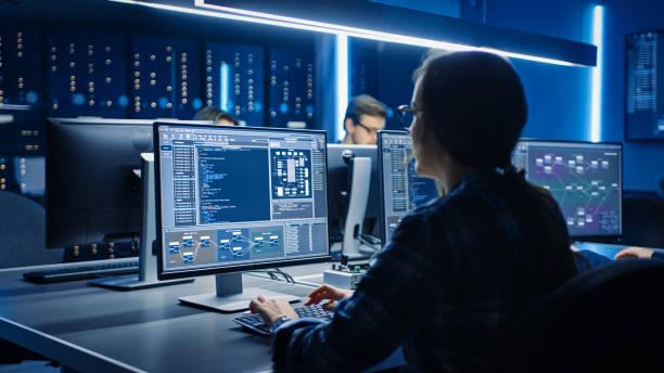 интеллектуальная женщина ит-программист работает на настольном компьютере в комнате управления системой центра обработки данных. команда - технологии стоковые фото и изображения