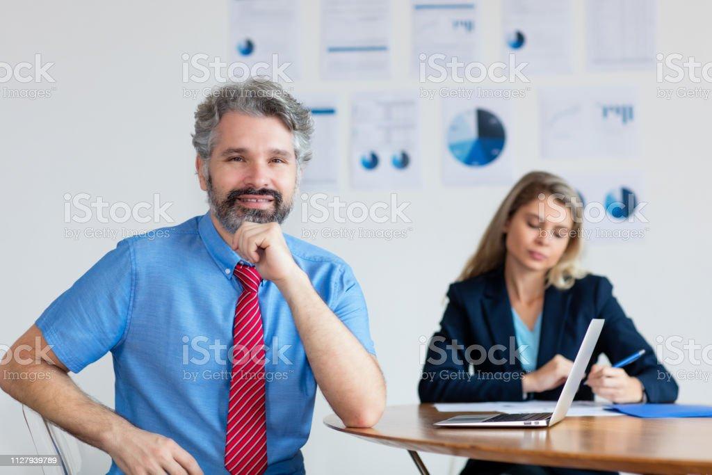 Inteligente hombre de negocios alemán con cabello gris y una computadora - foto de stock