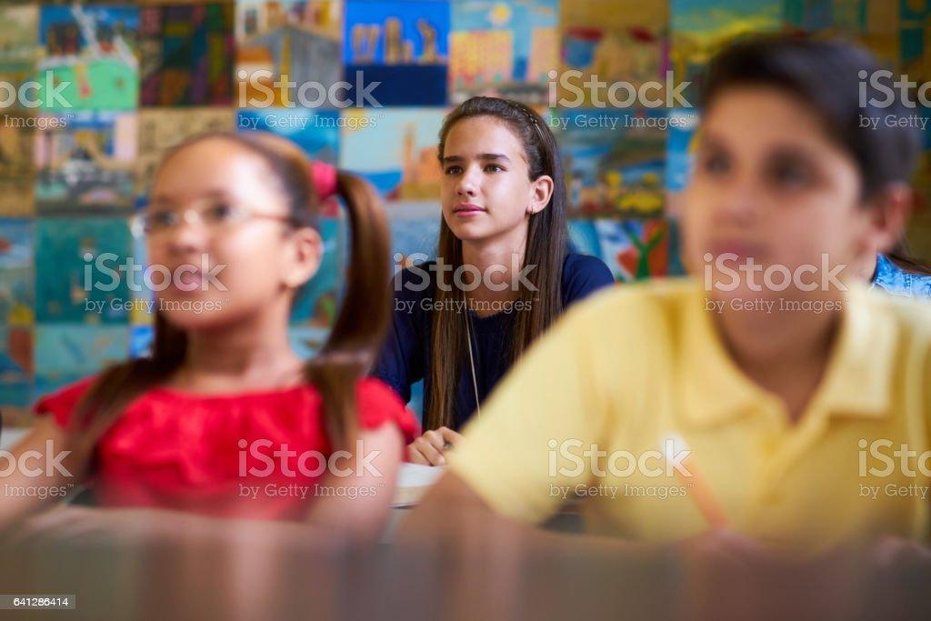 Chica inteligente escuchar al maestro en la escuela - foto de stock