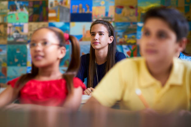 smart girl listening to teacher at school - middle school teacher stock pictures, royalty-free photos & images