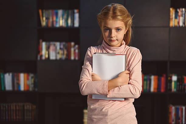 Smart girl with book in hands stock photo