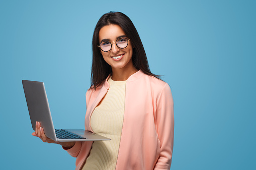 Young casual brunette in eyeglasses holding laptop and smiling at camera on blue.