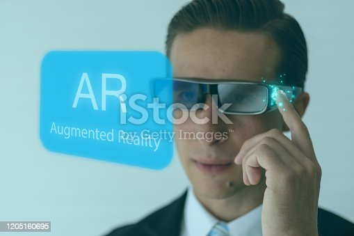 1150202730 istock photo smart glasses futuristic technology concept, man wear smart glasses an augmented mixed virtual reality with artificial intelligence combine deep, machine learning, digital twin, 5G, industry 4.0 tech 1205160695
