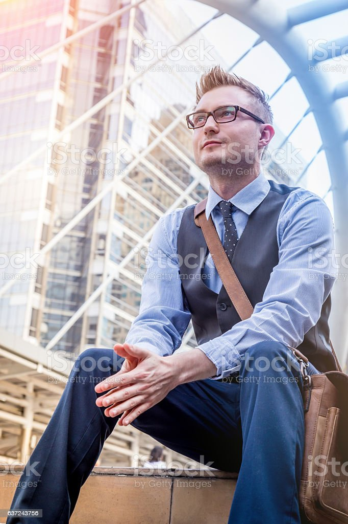 smart handsome american Businessman sitiing outside office building urban background stock photo