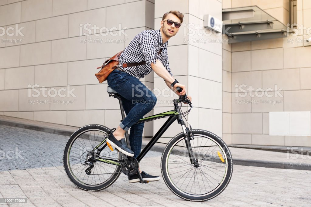 Smart handsome man riding a bike in the city stock photo