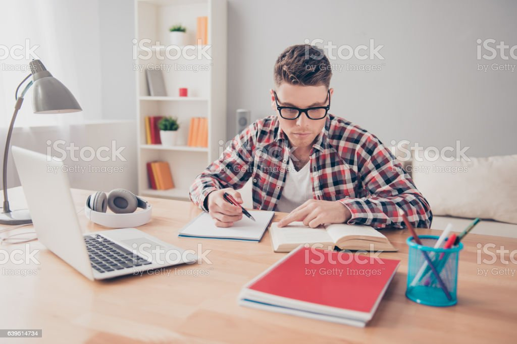 Smart handsome young man with notebook writing a lecture stock photo