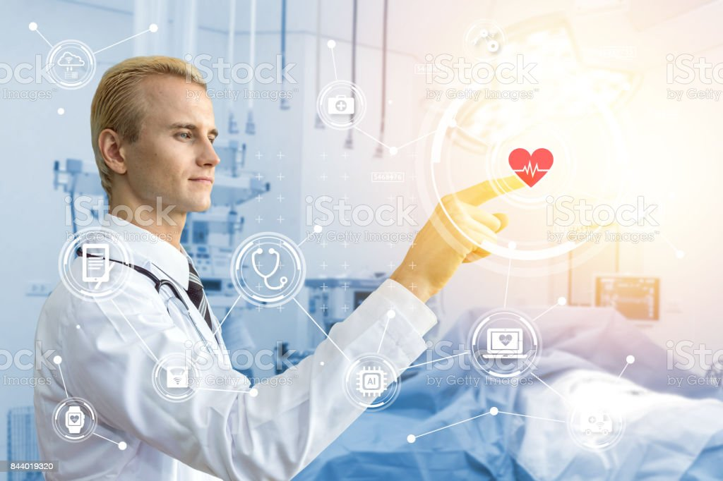 Smart healthcare technology concept. Doctor point finger and blur operation room background in hospital with icons graphic. Blue tone image and flare light effect. stock photo