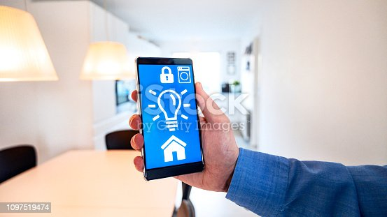istock Smart home app on mobile phone wirelessly controls light bulbs in lamps 1097519474