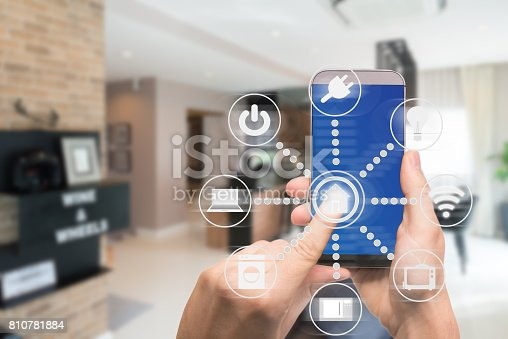istock Smart home automation app on mobile with home interior in background. Internet of things concept at home. Smart technology 4.0 810781884