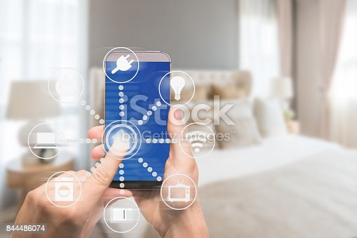 istock Smart home automation app on mobile with home interior in background. Internet of things concept at home. Smart technology 4.0 844486074