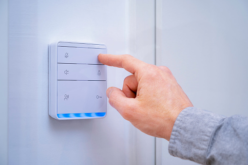 Finger pressing on the button of a smart home hub which controls the lights, thermostat and other electronics in the home of the future.