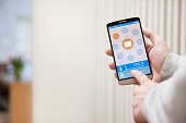 adjusting the room temperature with smart home automation system, with shallow depth of field and out of focus radiator
