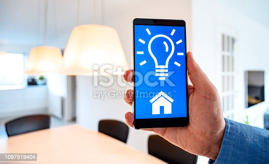 Concept of internet of things integrated in a smart home. Hand holds mobile phone with an app that controls the lighting bulbs in the house.