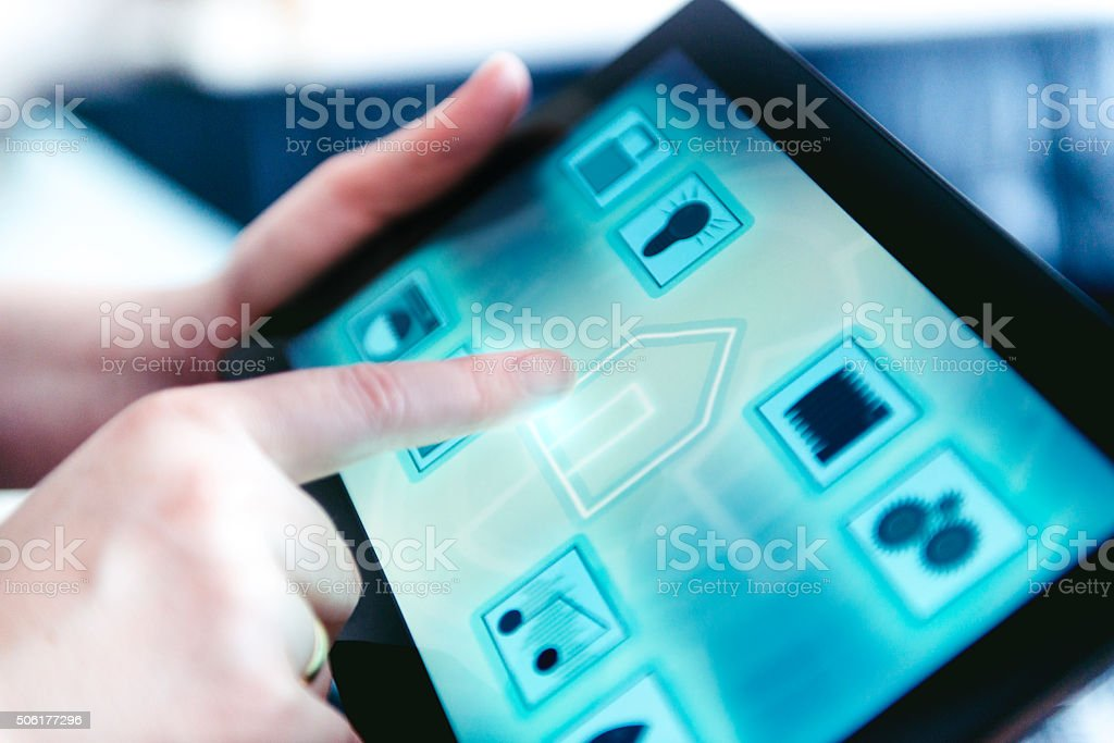 Smart home automation with app on tablet Tablet with an app controls several features in the home such as door lock, lights, washing machine, surveillance camera, music, water use and more. Woman press the tablet, that shows a icon of a house.  Accessibility Stock Photo