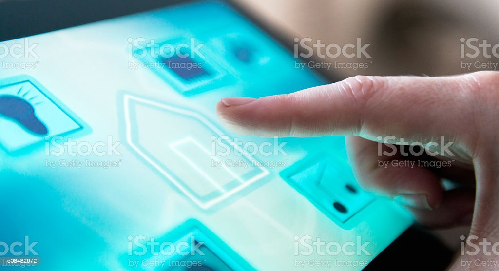 Smart home automation with finger on touch screen stock photo