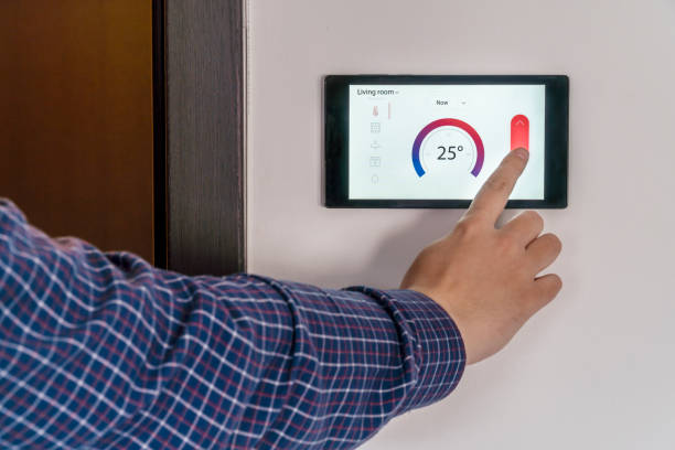Smart home climate control device on a wall stock photo