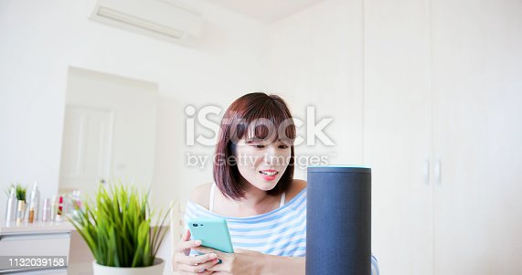 IOT AI smart home concept - woman talk with voice assistant to turn on the air conditioner