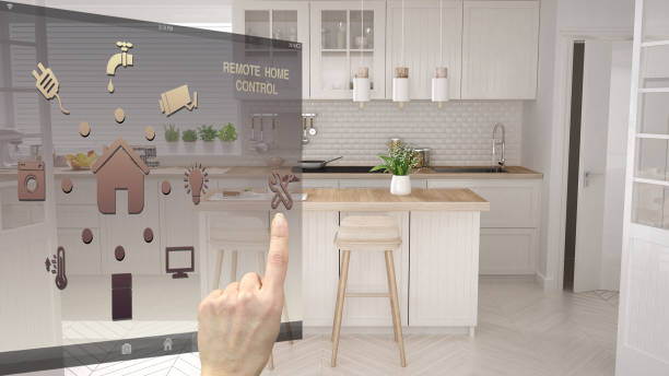 Smart home control concept, hand controlling digital interface from mobile app. Blurred background showing modern white modern scandinavian kitchen, architecture interior design stock photo