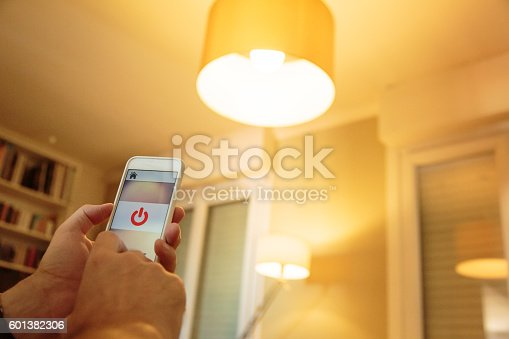 istock Smart home: man controlling lights with app on his phone 601382306