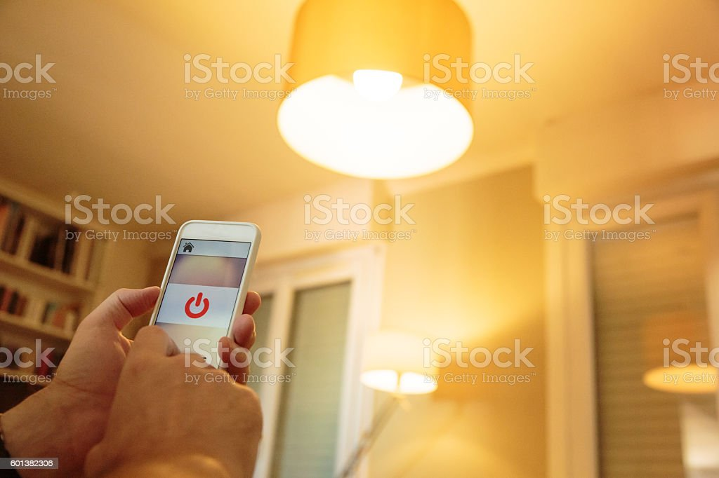 Smart home: man controlling lights with app on his phone stock photo