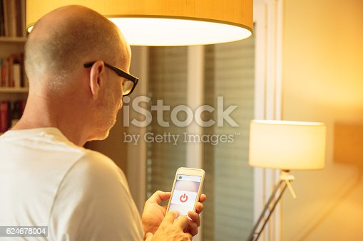 istock Smart home: man controlling lights with app on his phone 624678004