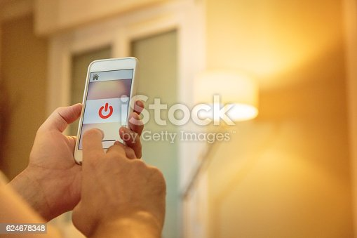 istock Smart home: man controlling lights with app on his phone 624678348