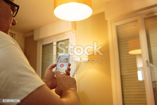 istock Smart home: man controlling lights with app on his phone 626698206