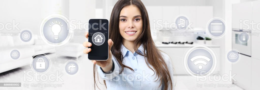 smart home smiling woman showing cell phone screen with symbols on kitchen and living blurred background stock photo