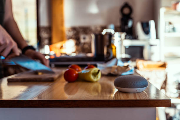 smart home speaker with woman cooking in the background. smart home ai device. - food delivery стоковые фото и изображения