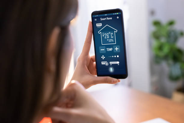 smart home system close up of asian young woman using smart home app on mobile phone to control air conditioner temperature smart thermostat stock pictures, royalty-free photos & images