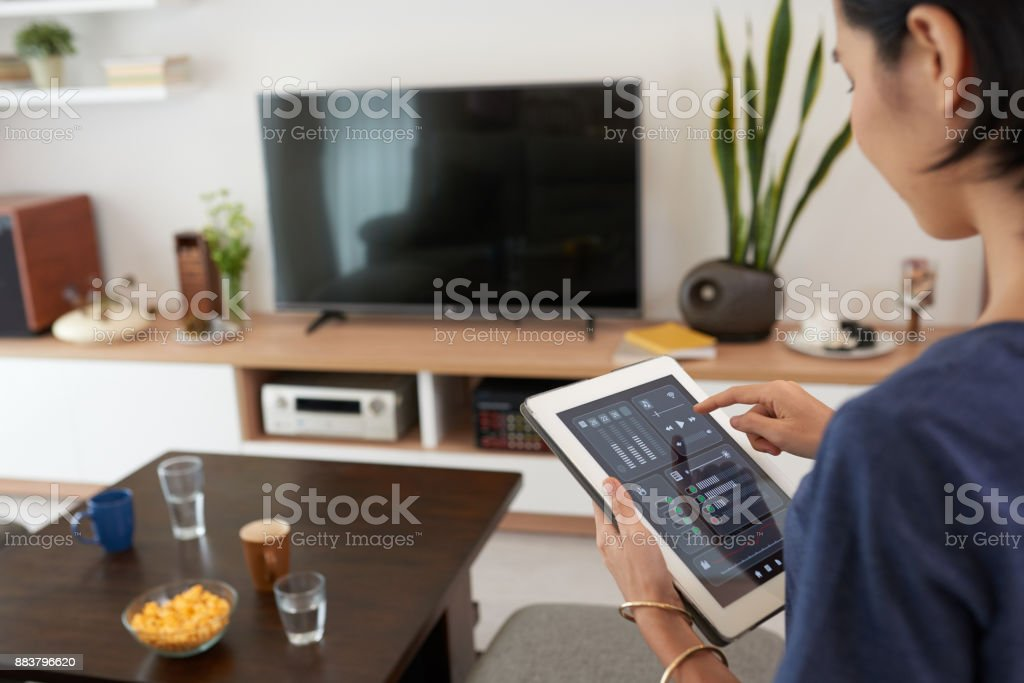 Smart home system Young woman using application in his smart home Adult Stock Photo