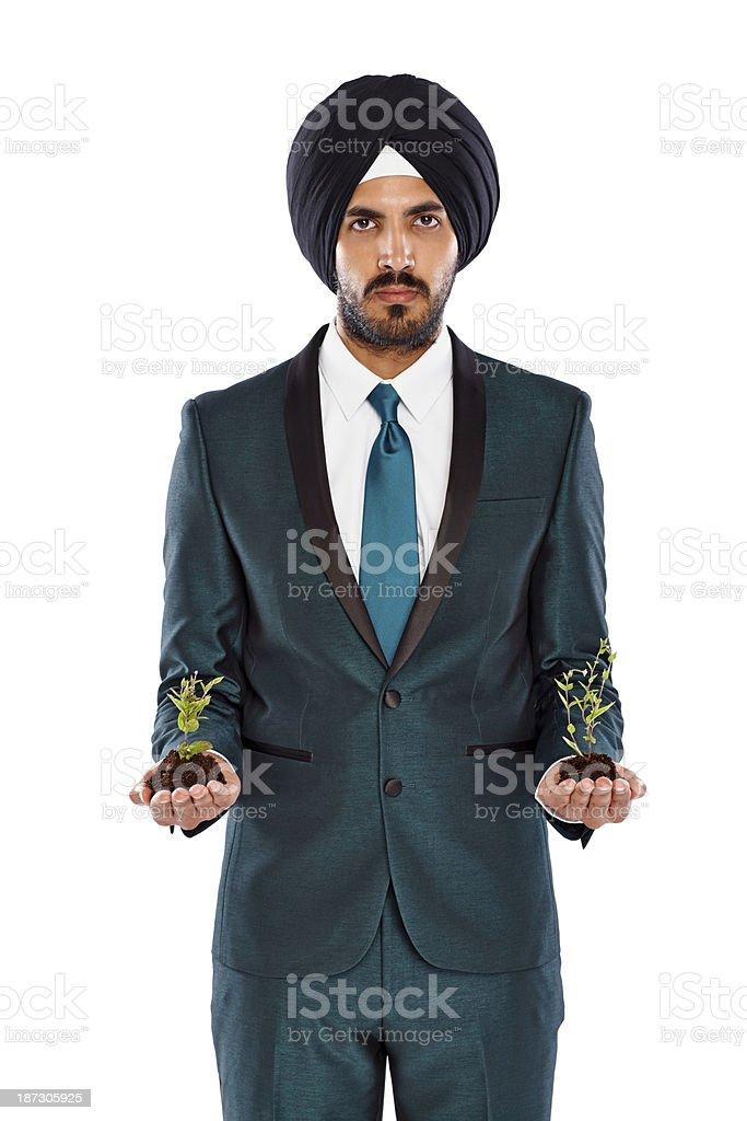 Smart Indian businessman holding seedlings royalty-free stock photo