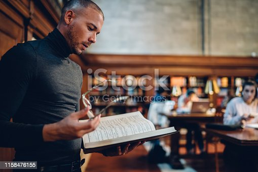 istock Smart intellectual male lawyer reading books making researcher for work while standing in public library, pensive concentrated journalist analyzing interesting information from literature manuals 1158476155