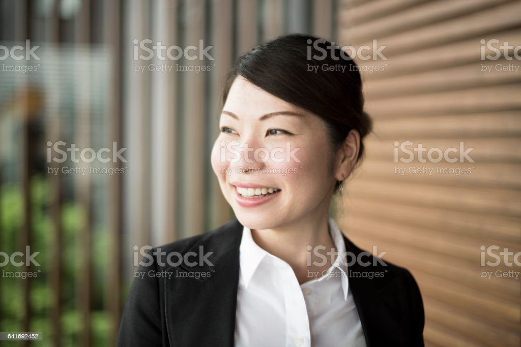 Smart Japanese businesswoman smiling and looking away stock photo