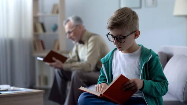 intelligentes kind in brillen und alten mann bücher zu lesen, ausbildung für verschiedene altersstufen - gedichte zum ruhestand stock-fotos und bilder