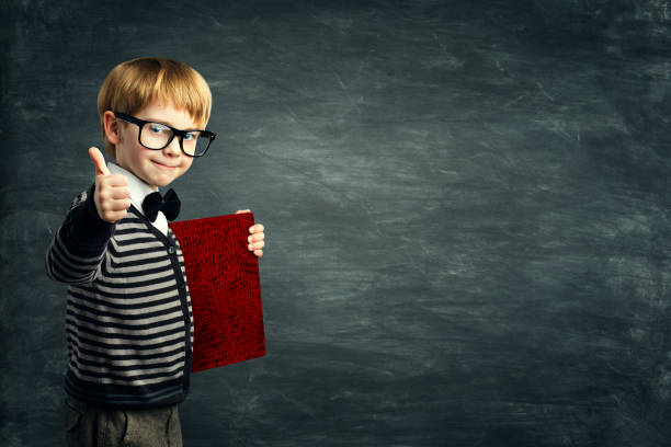 Smart Kid in Glasses, School Child Advertising Book Blank Cover, Boy showing Thumbs Up, Blackboard stock photo